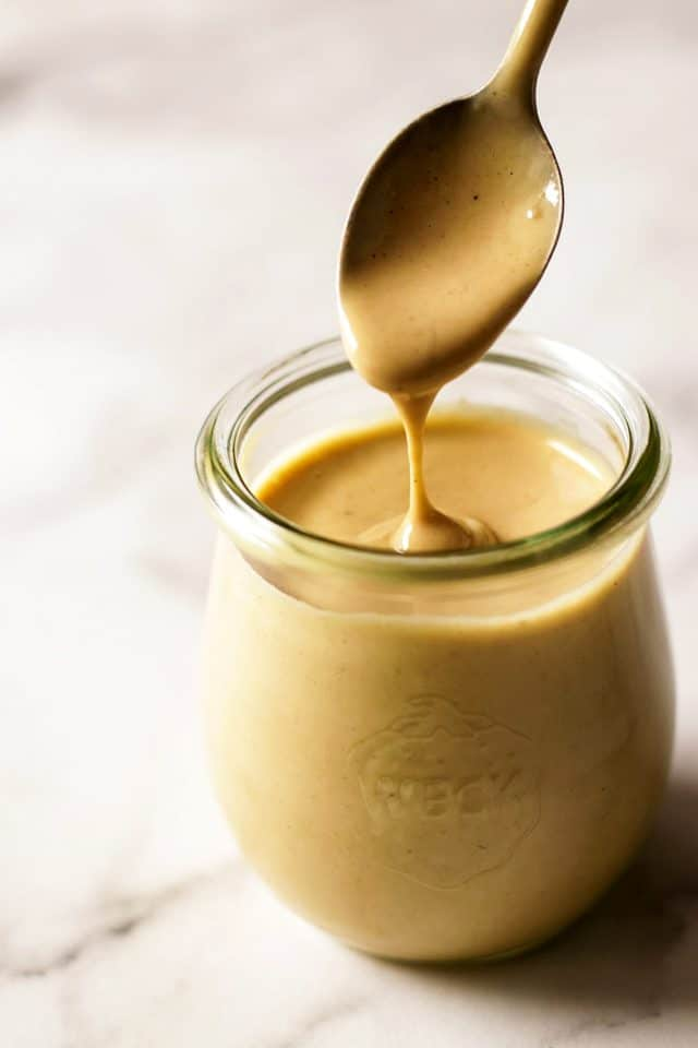 Tahini Dressing Dripping from a Spoon into a Jar