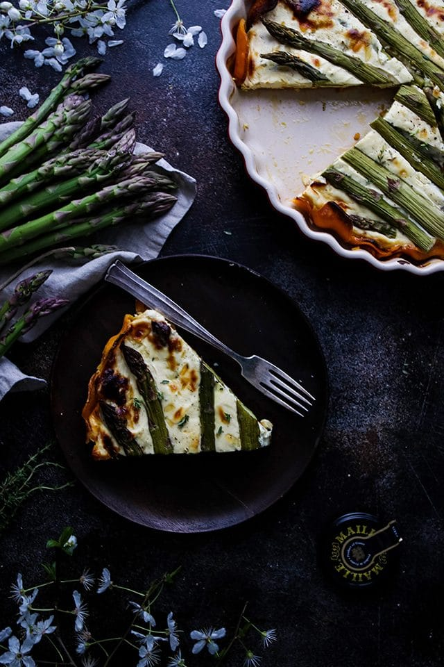 A Slice of Quiche on a Wooden Plate Next to a Pie Pan and Fresh Asparagus Spears