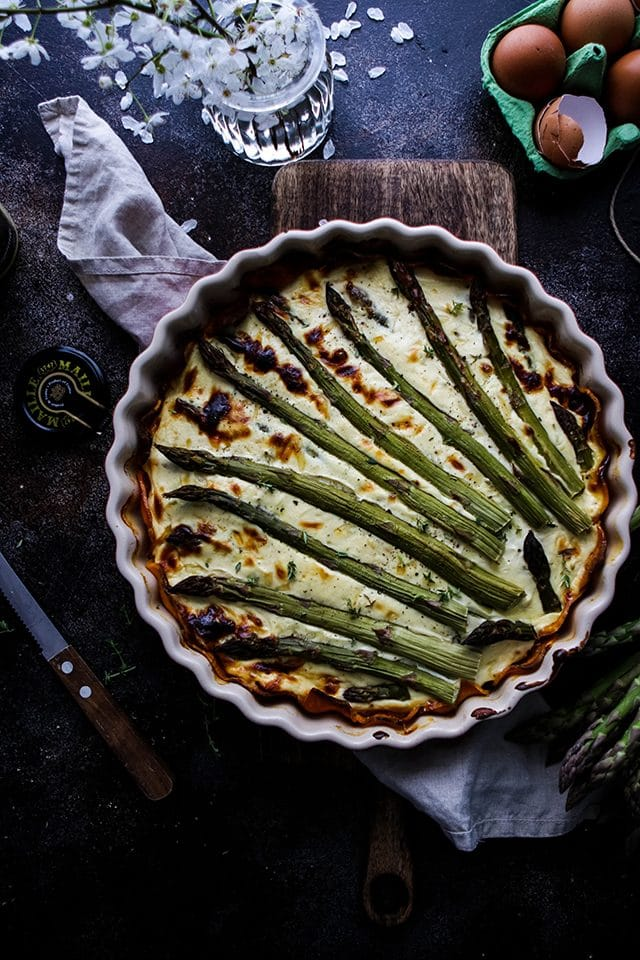 Asparagus Quiche in a Pie Pan After Baking Next to Eggs and a Knife