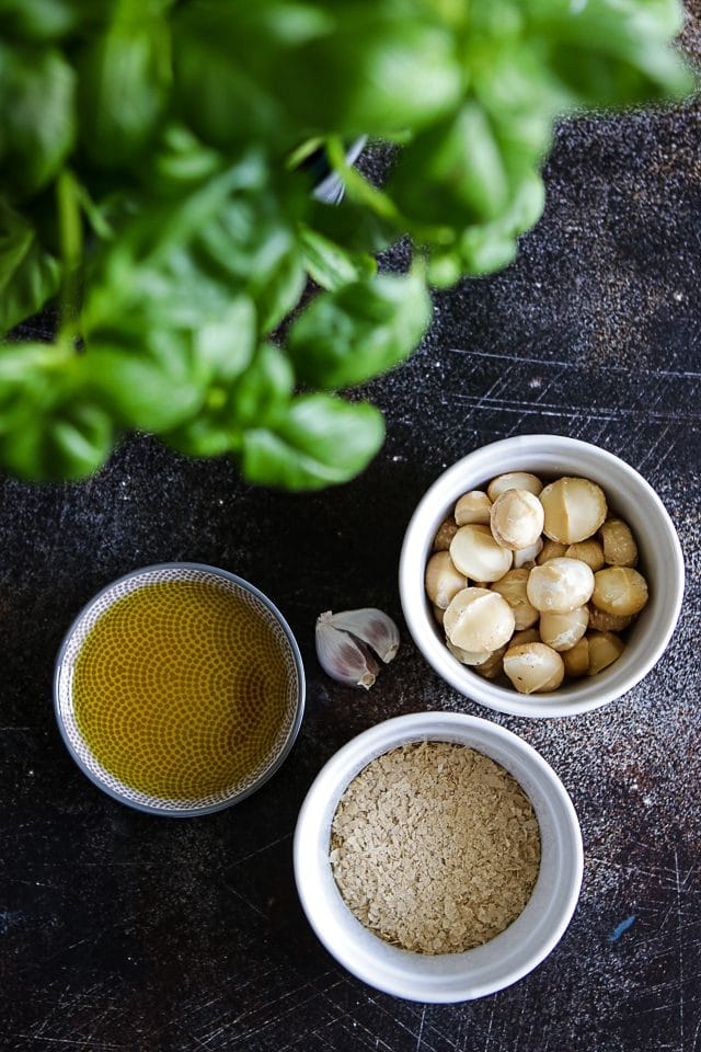Ingredients for vegan pesto: basil, nutritional yeast, macadamia nuts and olive oil