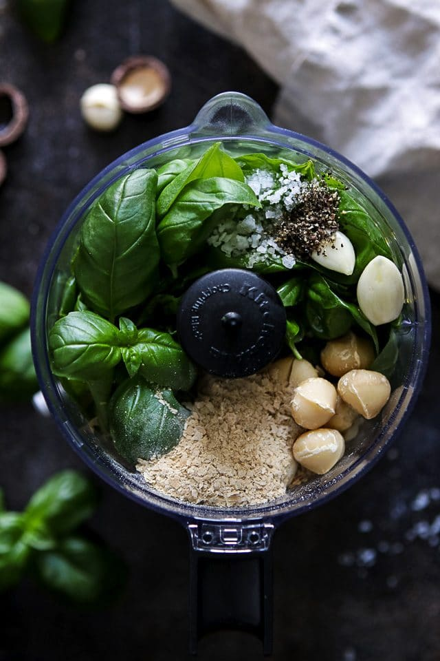 Ingredients for Pesto in the Chopper: Basil Leaves, Macadamia Nuts, Nutritional Yeast, Garlic Cloves, Olive Oil, Salt and Pepper