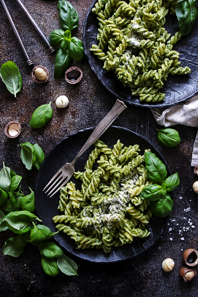 The Bowl of Vegan Pesto Pasta Garnished With Basil Leaves and Chopped Macadamia Nuts