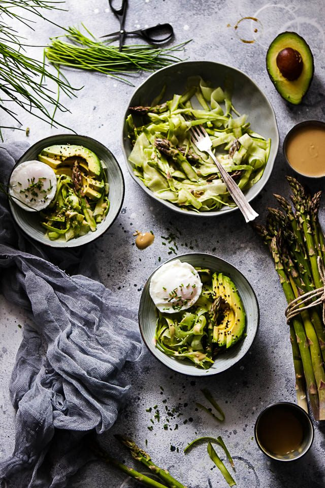 Three Bowls of Shaved Asparagus Salad on Grey Background Next to Asparagus, Peanut Dressing and Chives