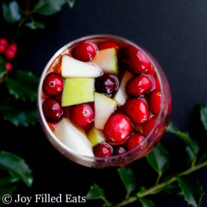apple cider sangria with cranberries in a glass.