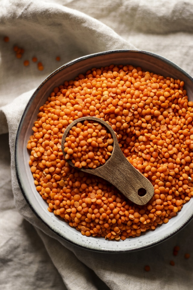 Raw Red Lentils in a Bowl with a Wooden Spoon