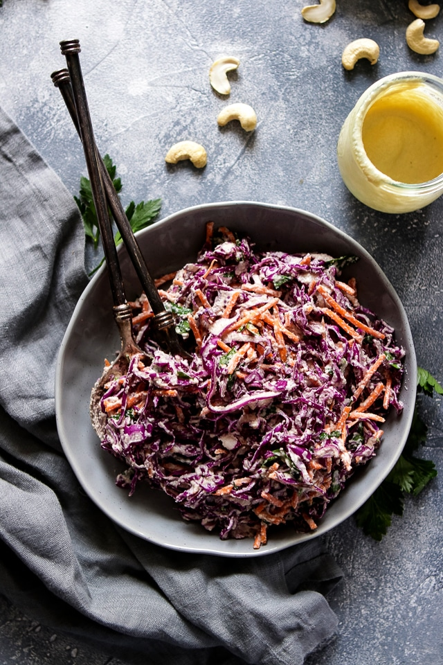 Coleslaw Salad on a Plate with Utensils Next to a Jar of Vegan Mayo