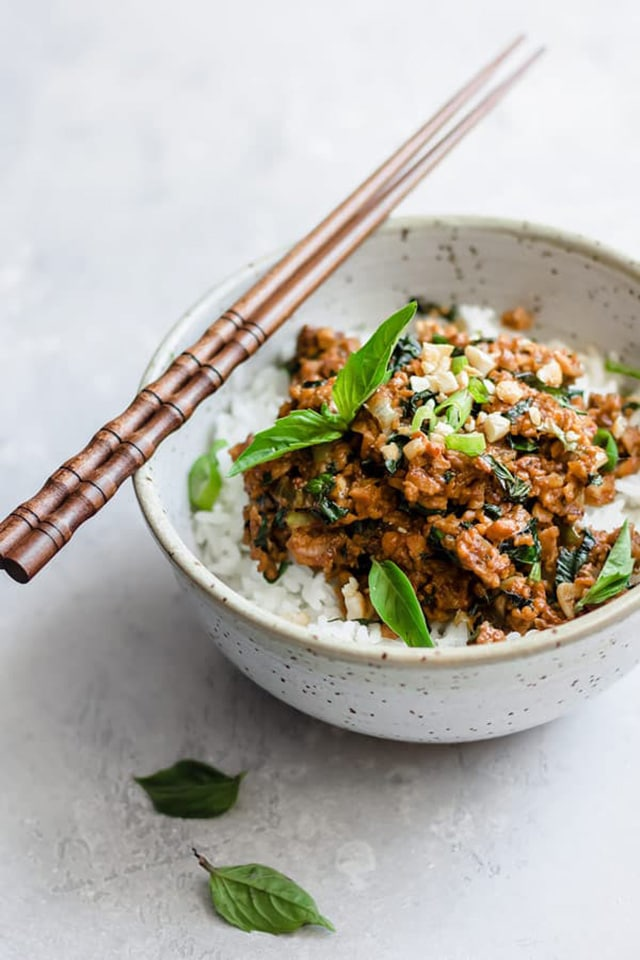 Thai basil tempeh stir fry ready and served in a bowl with two sticks on top
