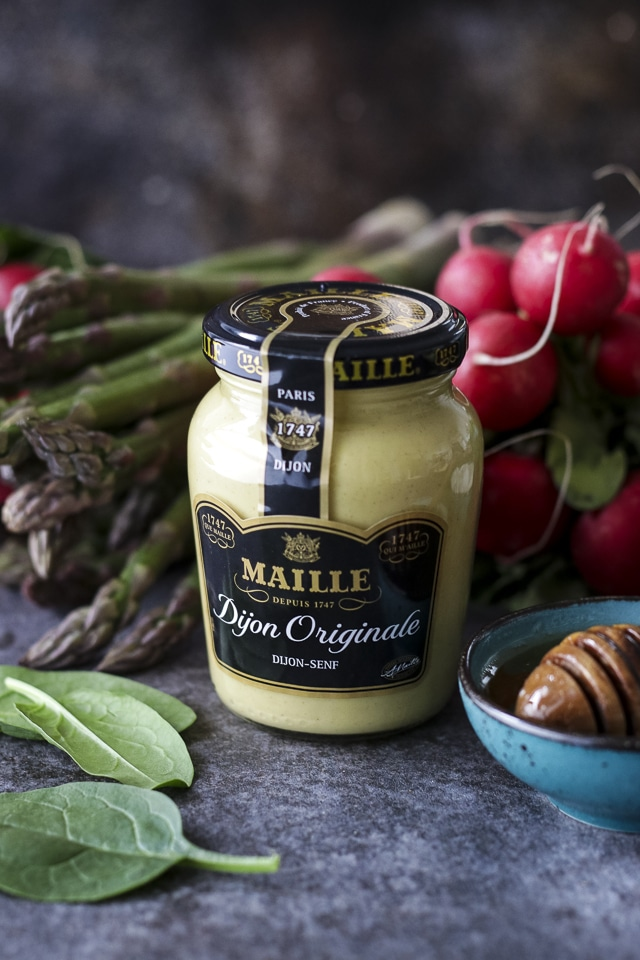 A Jar of Maille Dijon Mustard Surrounded by Spring Vegetables