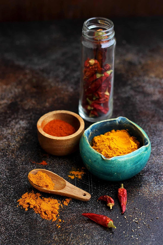 Spices in Bowls and Spoons on a Dark Background