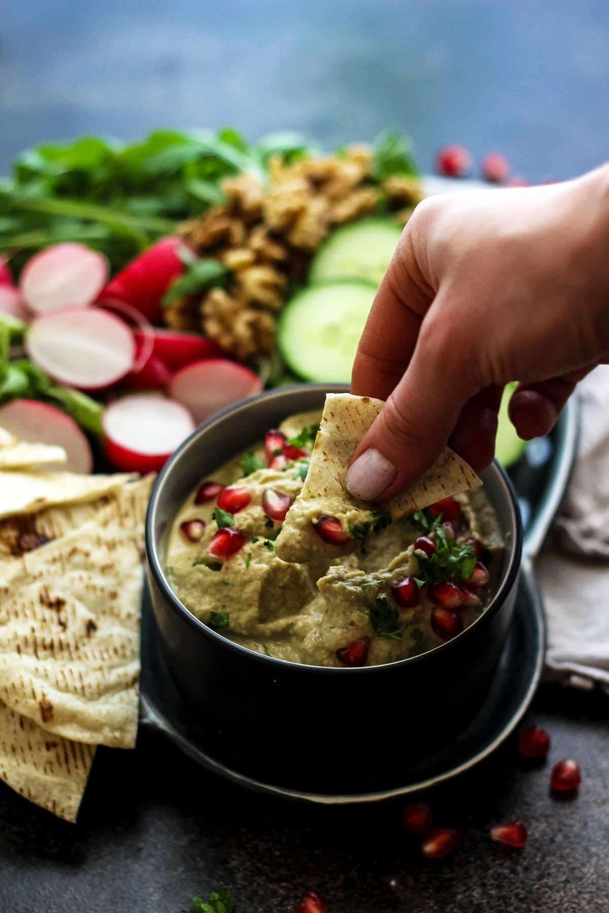 Dipping Pita Chips in an Eggplant Dip