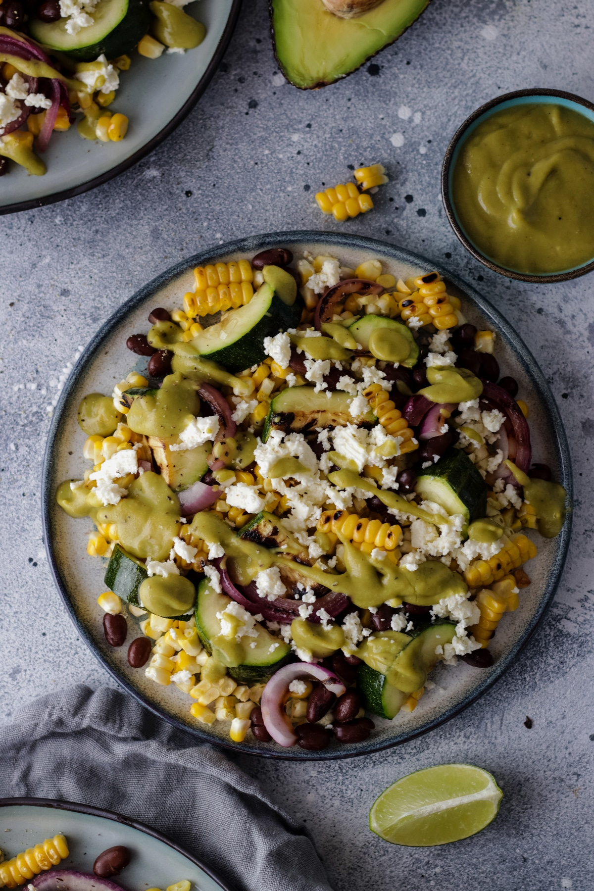 A Plate with Grilled Corn and Black Bean Salad Next to a Bowl with Avocado Dressing