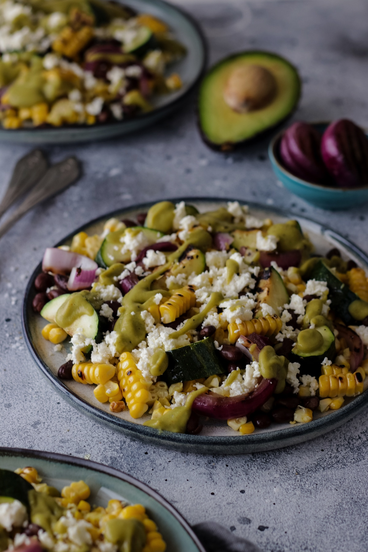 Corn Zucchini Salad on a Plate Surrounded by Ingredients