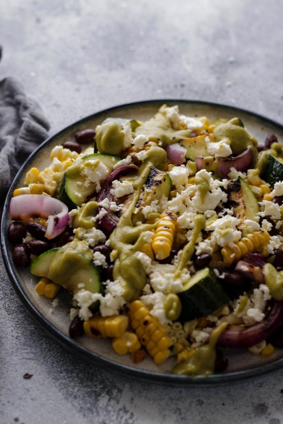 Grilled Zucchini and Corn Salad with Black Beans on a Plate on a Grey Background