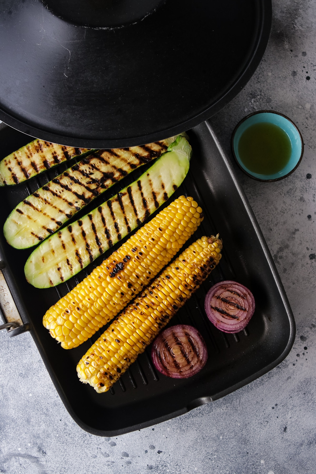 Grilling Corn Zucchini and Onion on a Griddle Pan