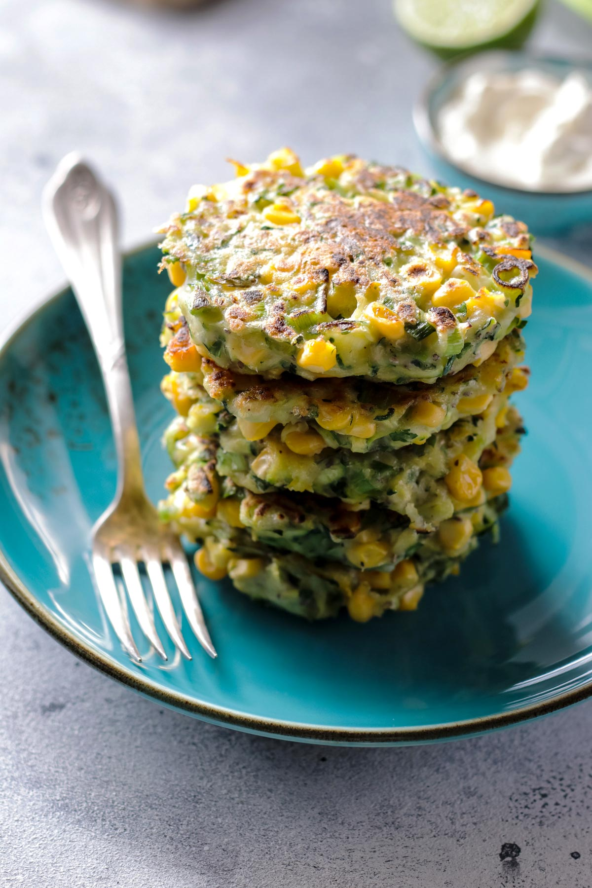 A stalk of zucchini corn fritters on a plate.