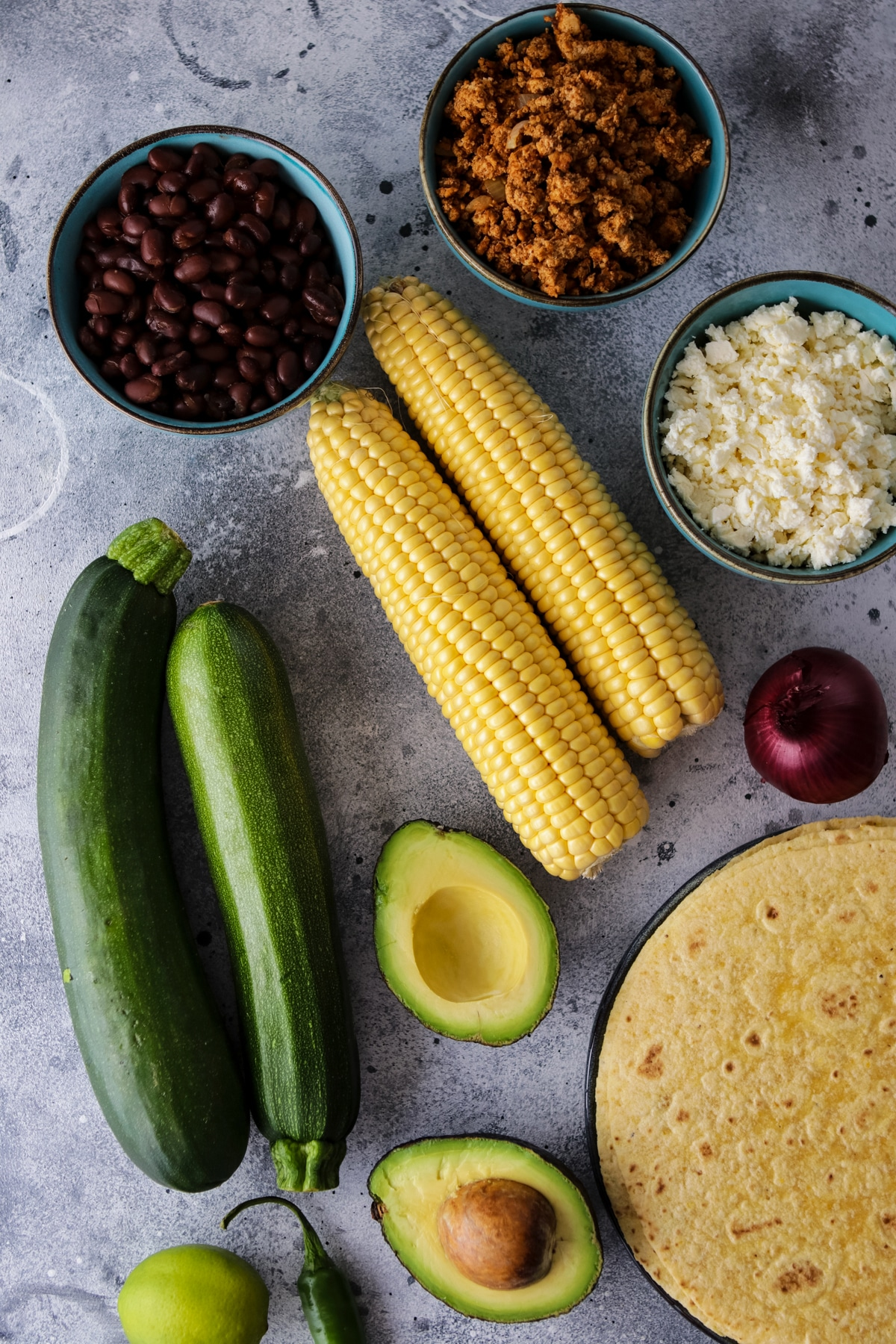 Ingredients for grilled tacos including zucchini, corn, avocado, tempeh taco meat, feta cheese, black beans, tortillas, etc.