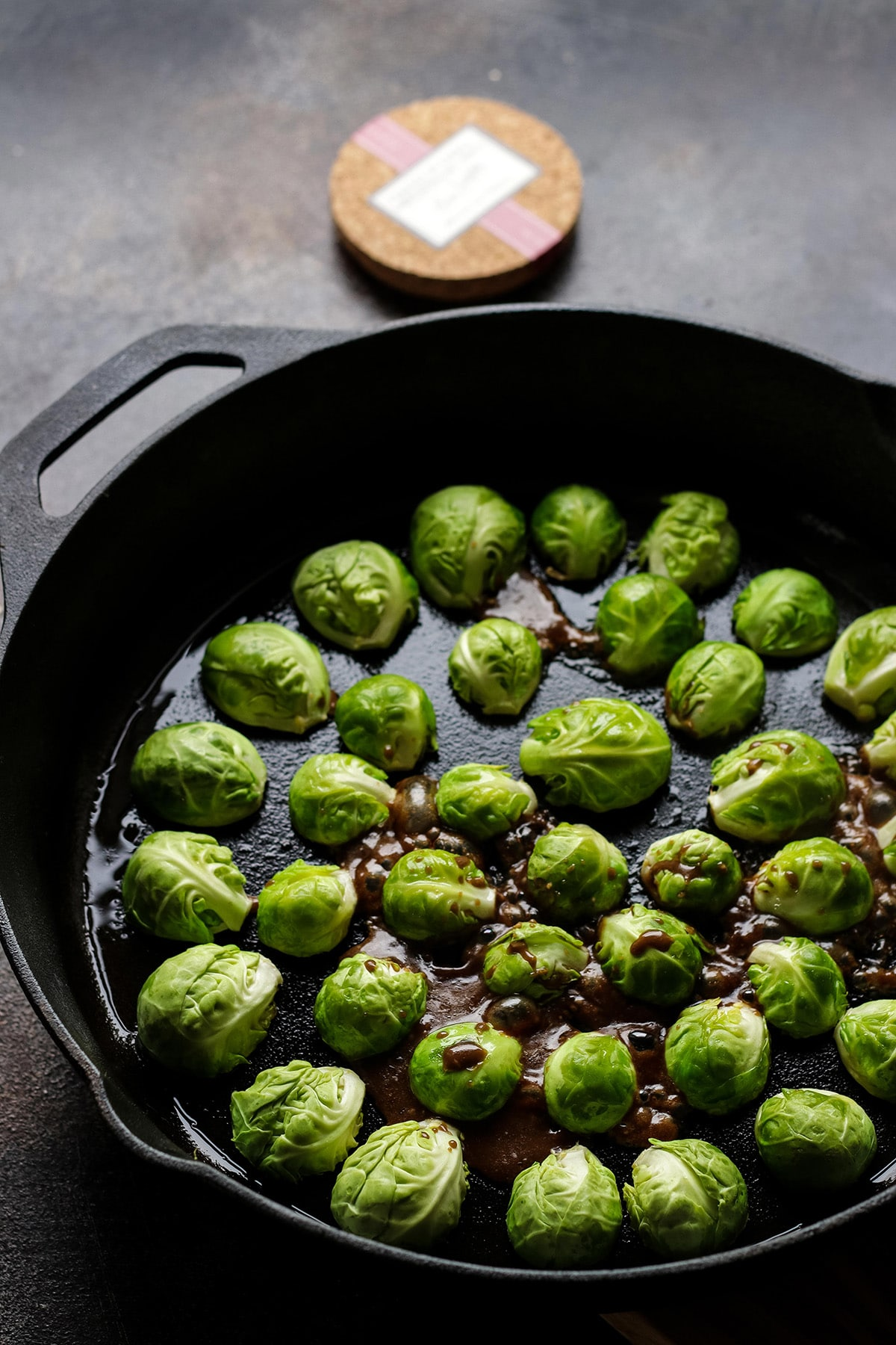 Adding Balsamic Glaze to Brussels Sprouts in a Skillet.