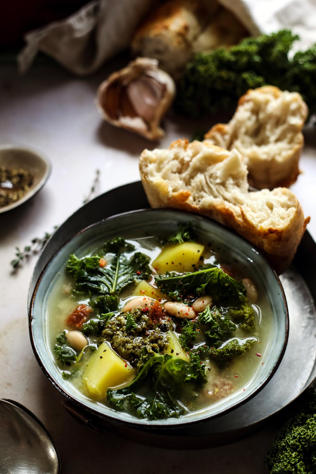 Potato and kale soup in a bowl served with crusty bread.