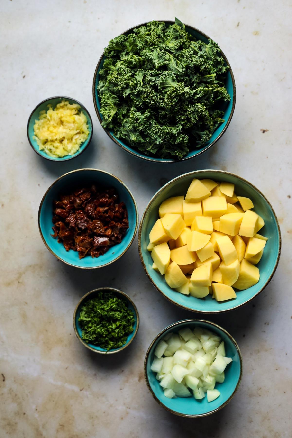 Prepped vegetables for kale potato soup in bowls.
