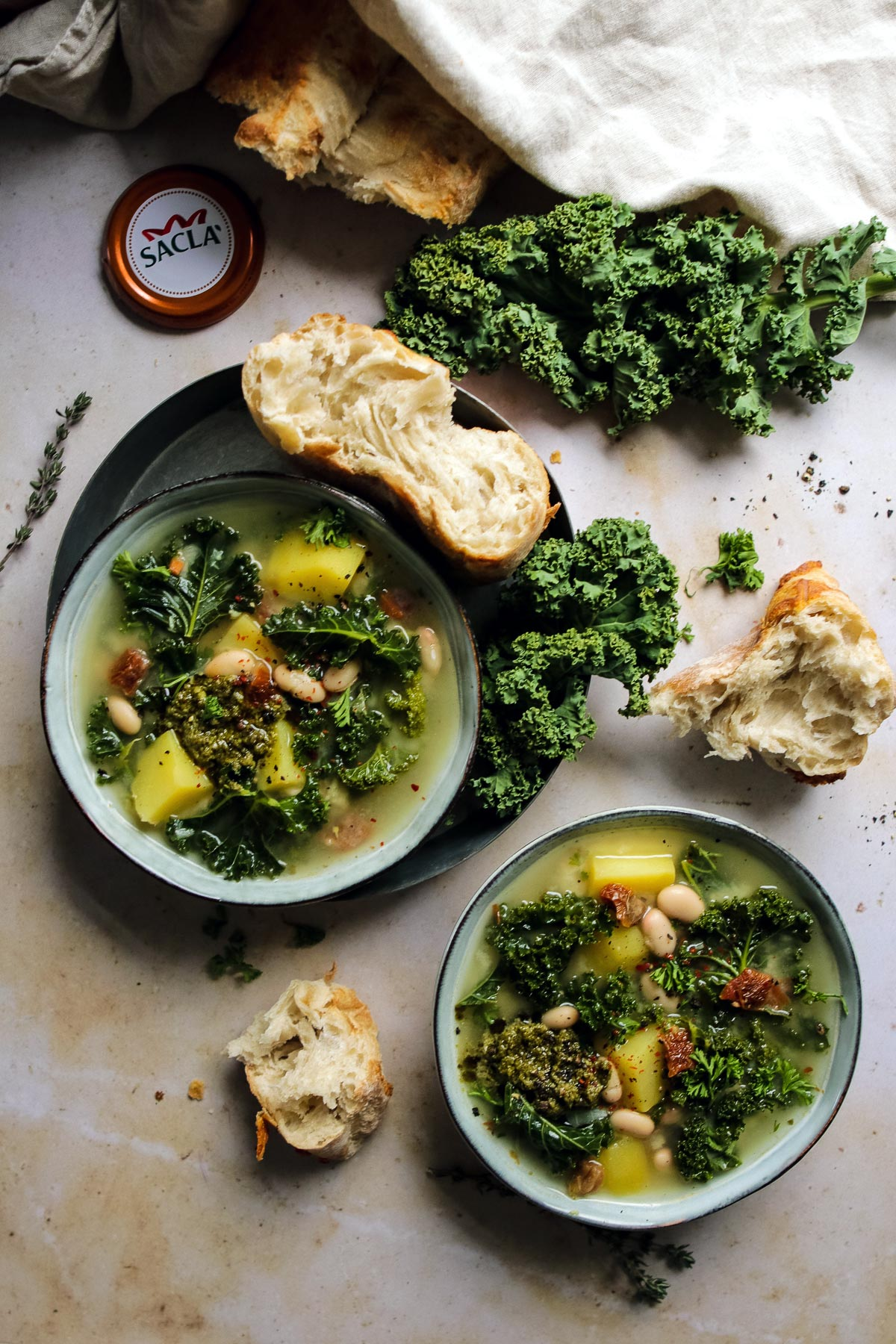 Two bowls with vegetarian Tuscan soup served with crusty ciabatta bread.