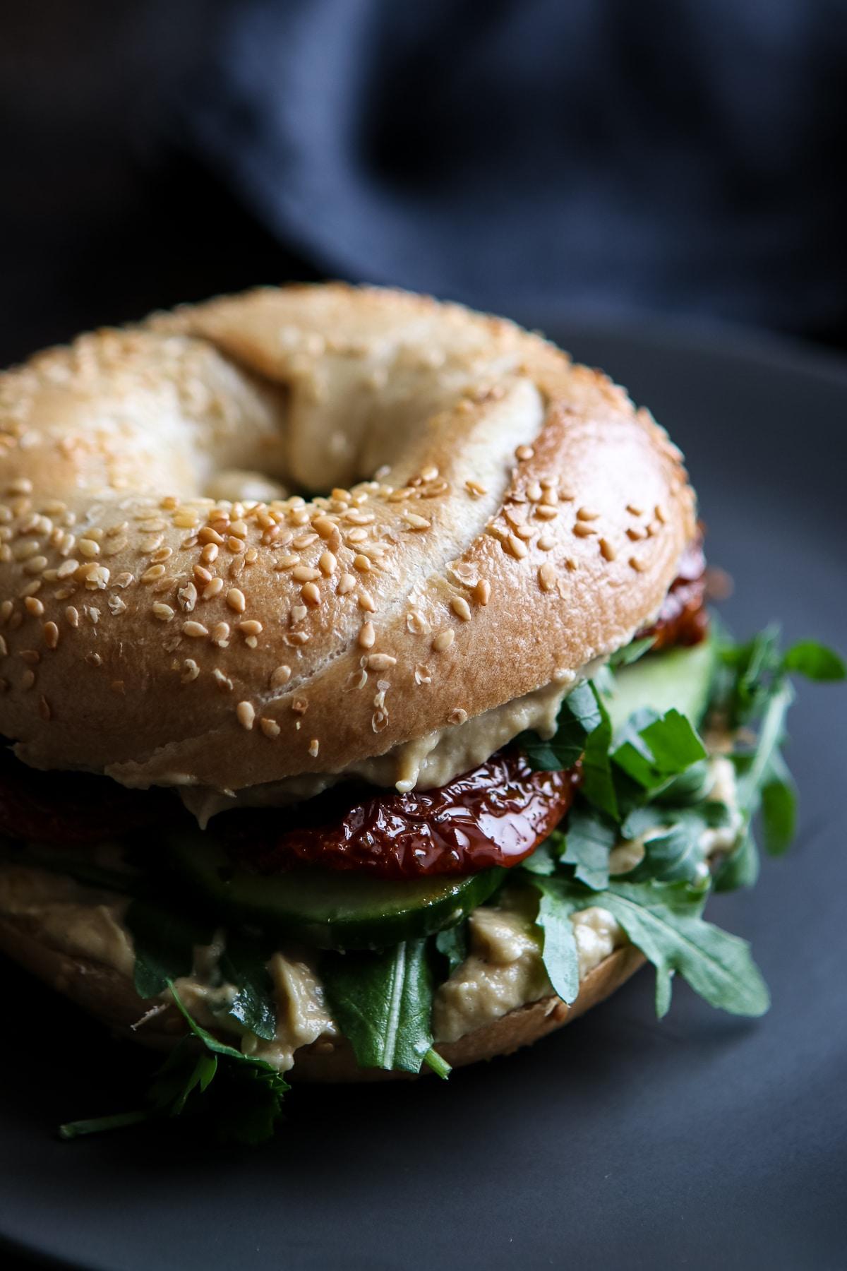 Vegan Bagel Sandwich on a Black Plate.