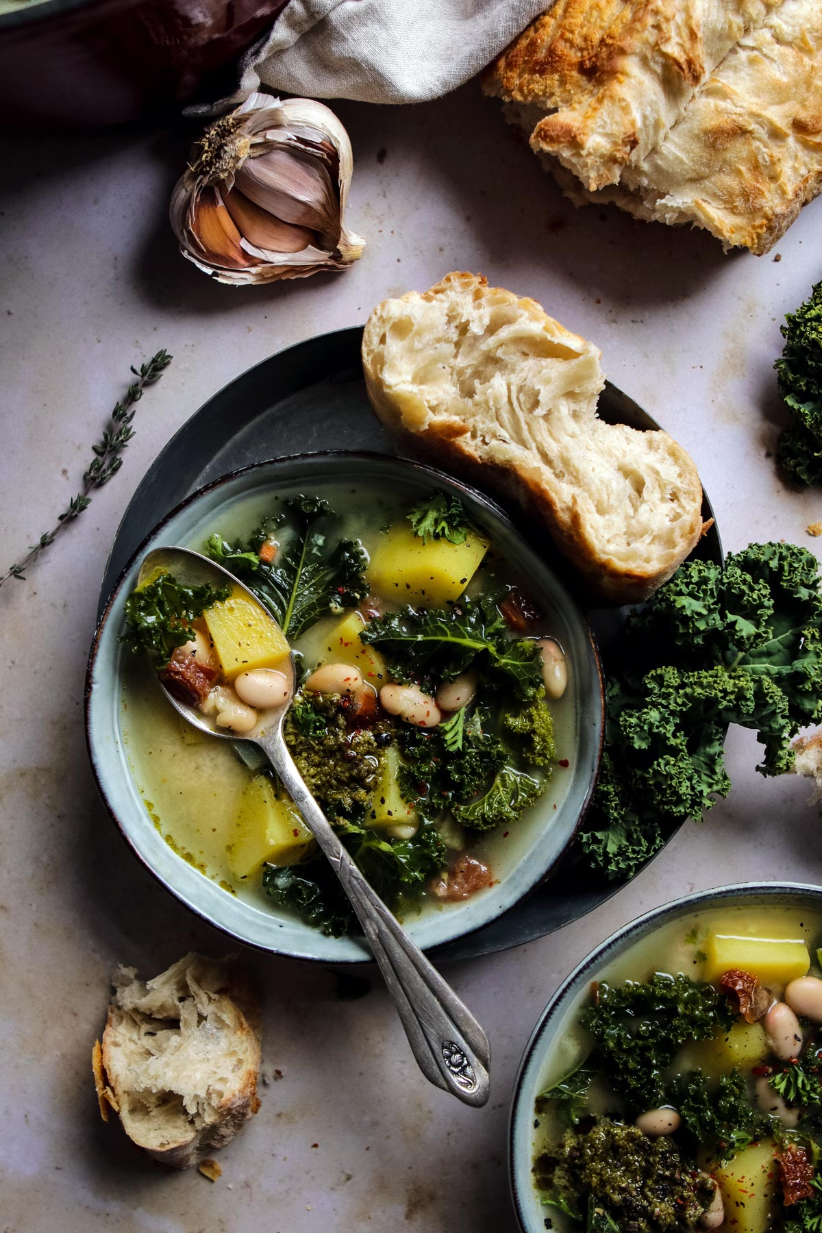 Vegan potato and kale soup in a bowl with a spoon.