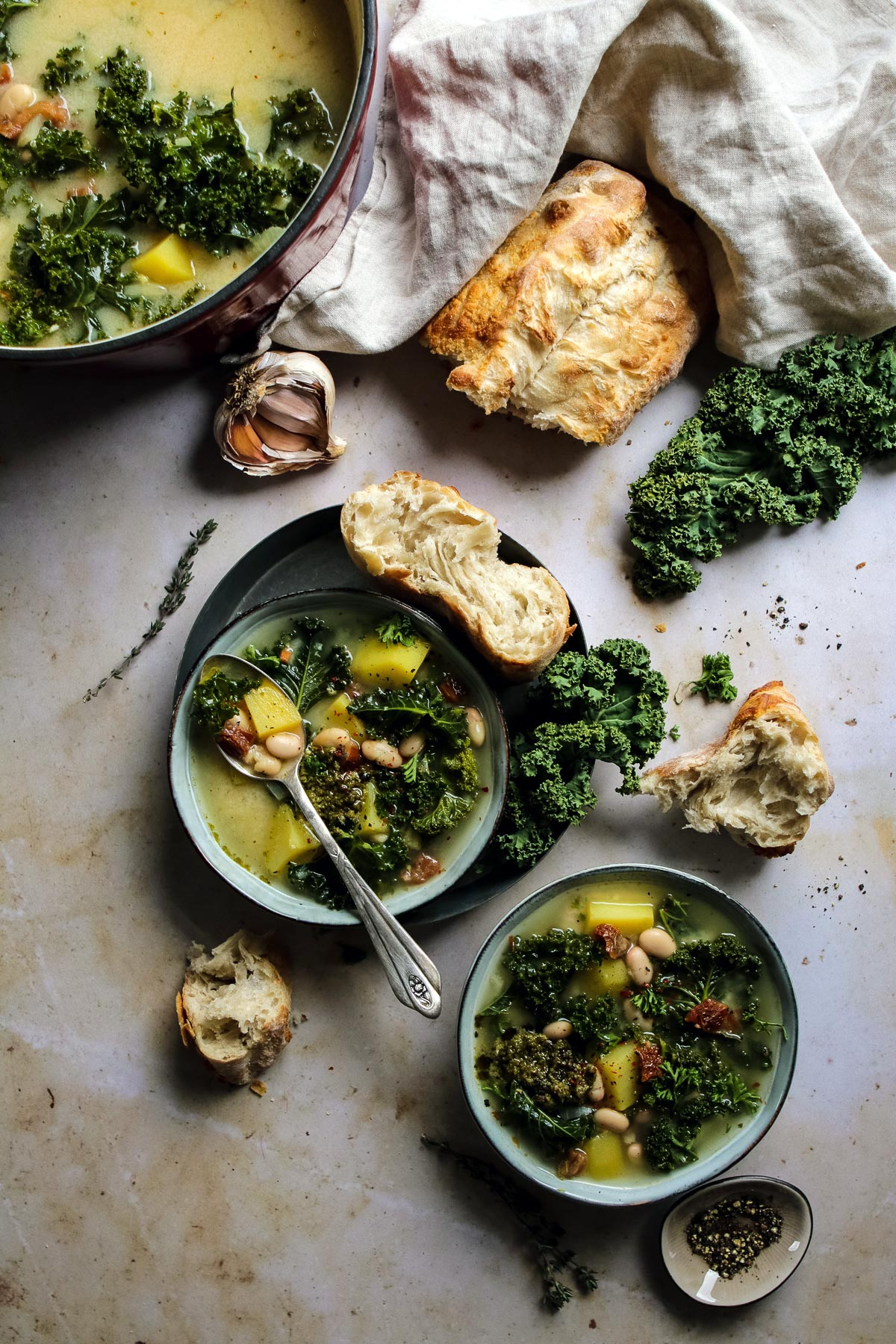 Vegan Zuppa Toscana in bowls with bread.