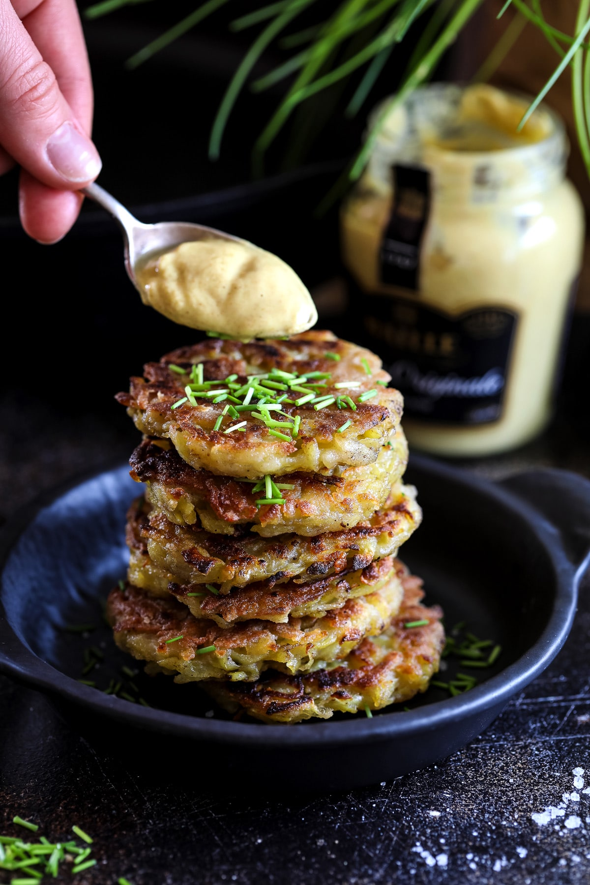 Adding Mustard to a Stack of Potato Pancakes.